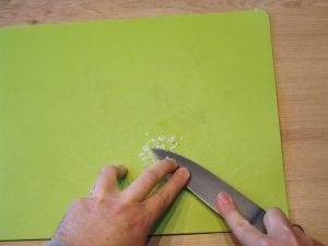 Das Messer wird mit Druck über den Knoblauch gezogen. Dabei wirkt das Salz wie Schmirgelpapier. (Bildrechte: FRAGDENSTEIN.DE/ Stein)