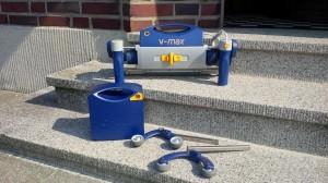 Die Rollstuhl-Schiebehilfe V-Max ist modular aufgebaut und besteht aus Akku, Motoreinheit, zwei Stützrädern und zwei Handgriffen. (Bildrechte: FRAGDENSTEIN.DE/ Stein)
